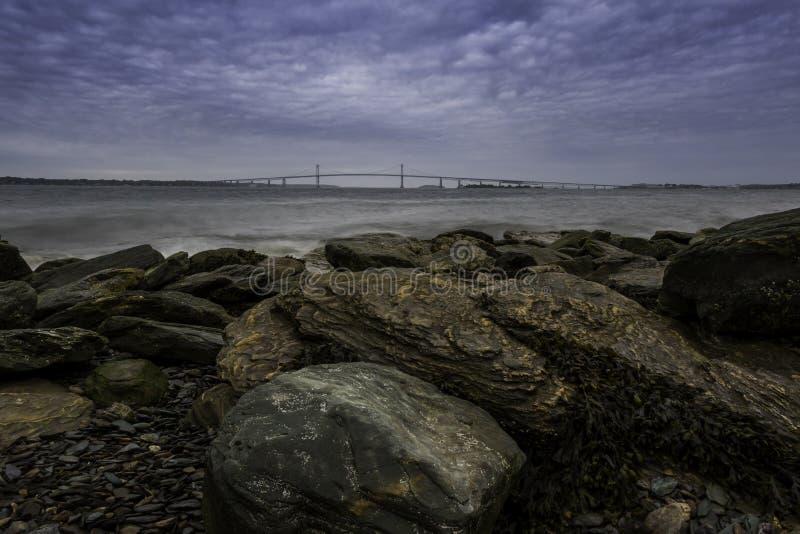 View of Ocean Bridge from Rocky Shore. Under dramatic cloudy sky. Newport Pell Bridge taken in Newport, Rhode Island royalty free stock image