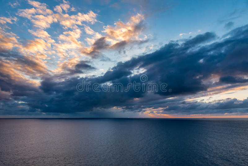 View of the ocean horizon with the sunseting and reflection on t. He clouds with storm clouds below stock photography