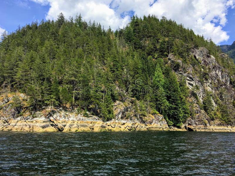 A view from the ocean of a rocky shore and steep rocky cliff covered by evergreen trees while boating in the pacific northwest. Near Vancouver, British Columbia royalty free stock images