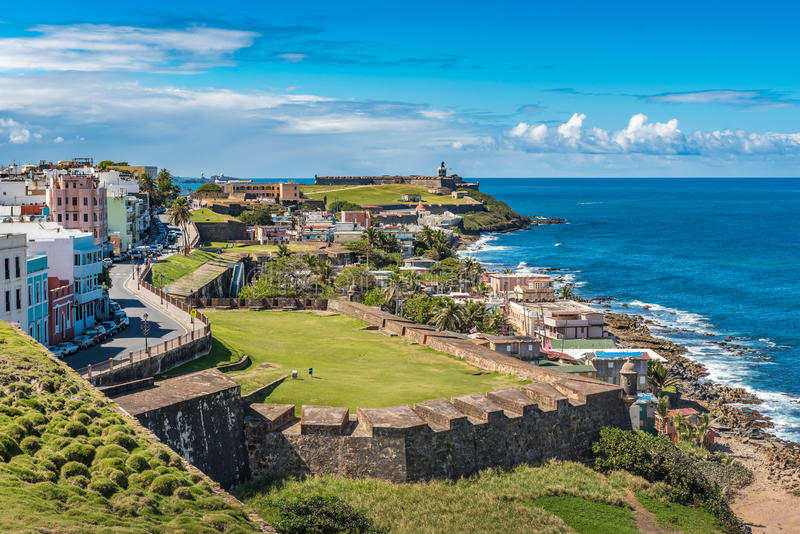 View of ocean towards San Felipe del Morro from Castillo de San. Cristobal with castle wall and grass fields in between stock photo