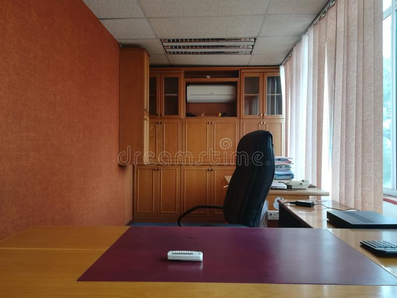 View in an office from across a desk looking at an empty chair. Empty desk. No people. Cabinets in the background royalty free stock image