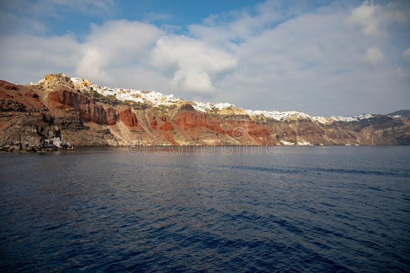 View of Oia village with white houses on red rocks caldera of Santorini Island, Greece royalty free stock photography