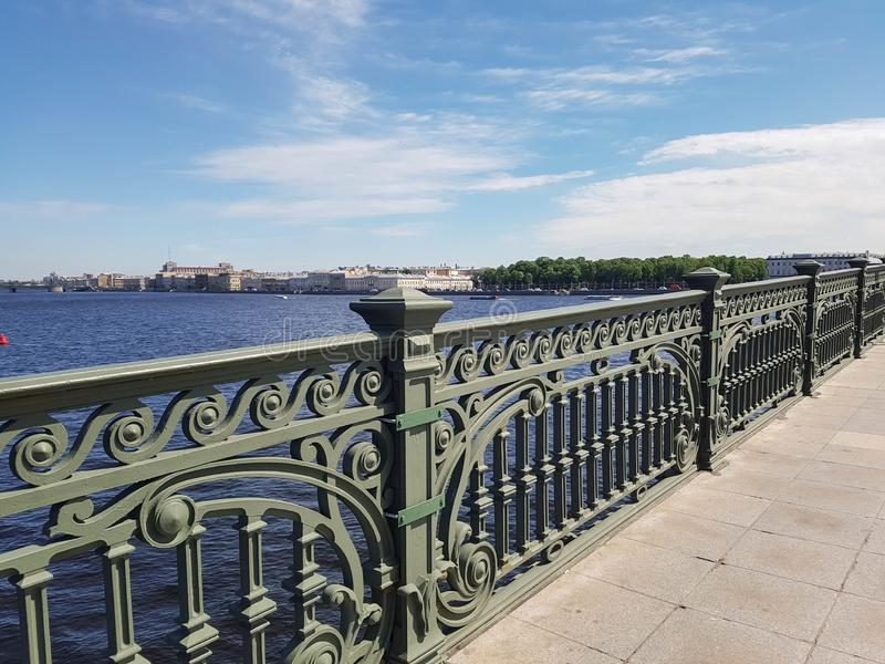View from the old bridge. Cast openwork railings, river water and sky stock photo