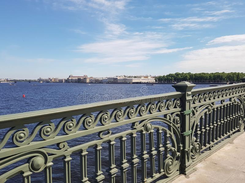 View from the old bridge. Cast openwork railings, river water and sky stock image
