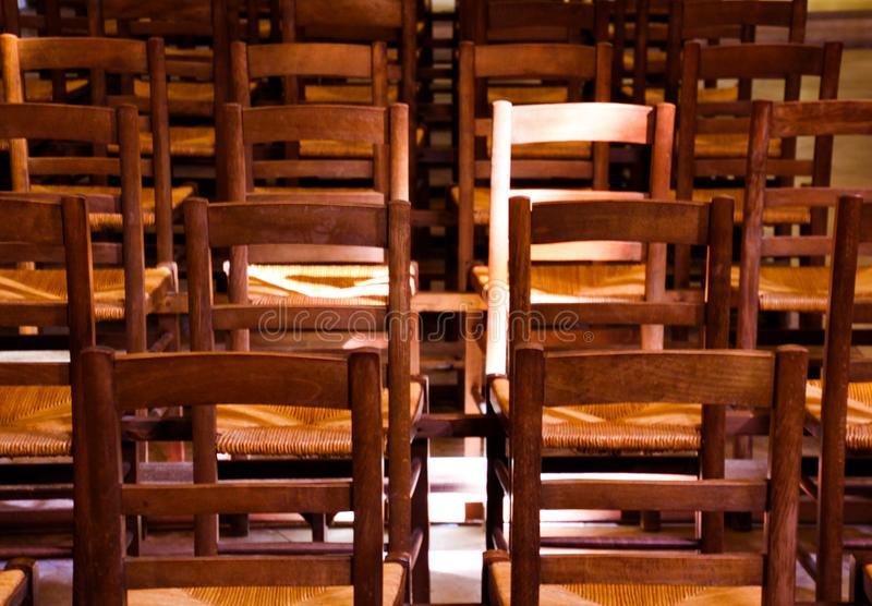 View on  old brown wood chairs with backrest in a row inside catholic empty church illuminated by natural sun light stock images