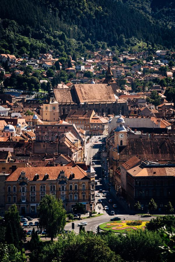 View of old city landmarks orange rooftops from above on Bright sunny day, Brasov, Transylvania, Romania. Vertical travel destination famous tourist attraction stock image