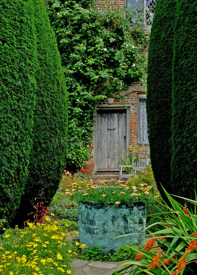 A view of an old country garden. With copper vase and summer flowers royalty free stock photography