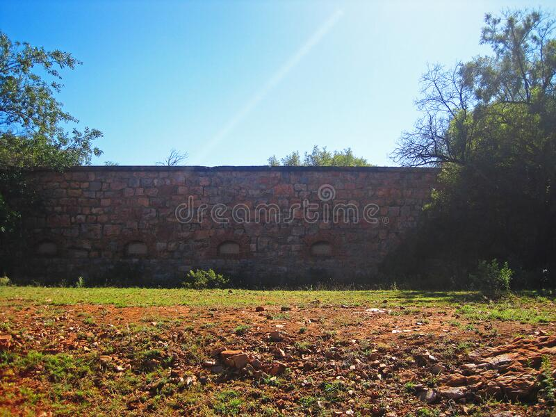 VIEW OF OLD FORT WALL IN MORNING SUNLIGHT. View of old fort wall from outside in bright morning sunlight in South Africa stock image