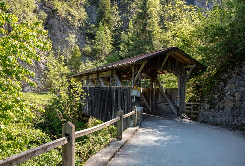 View of an old historic covered wooden bridge. With high mountains in the background in the swiss alps royalty free stock image