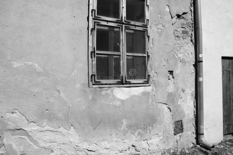 View of an old house with cracks on the wall and window, black and white photo.  royalty free stock photo