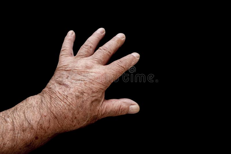 Mans reaching hand. A view of old mans hand reaching out on a black background stock image