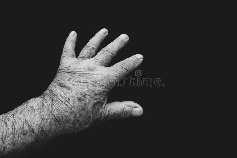 Mans reaching hand. A view of old mans hand reaching out on a black background royalty free stock image