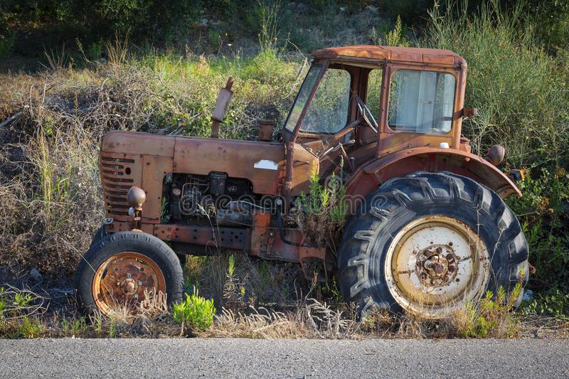 View of an old rusted tractor parked in nature. View of an old rusted tractor parked in nature, Peloponnese - Greece stock photo