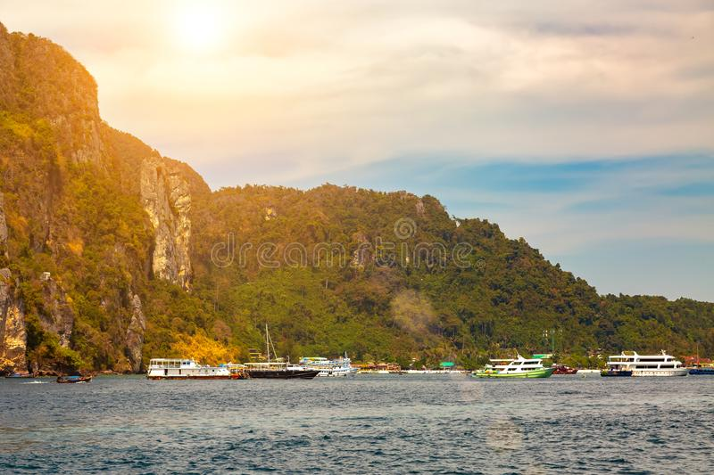 View on old seaport on a tropical island from the water. Colorful ships on the background of cliffs. Sunny day with clouds, blue royalty free stock photos