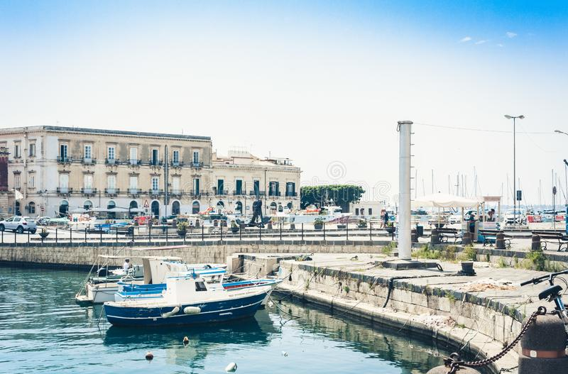 View of old street, facades of ancient buildings and sail boats in seafront of Ortygia Ortigia Island, Syracuse, Sicily, Italy.  stock images