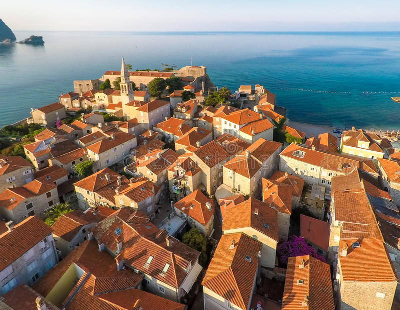 View of old town Budva from the top: Ancient walls and tiled roo. F of old town Budva, Montenegro, Europe. Aerial shoot stock image