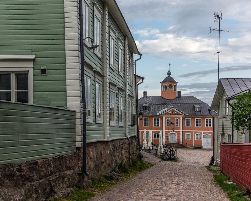 View of the old Town Hall of Parvoo now a Museum with the Cocbled streets and colorfully painted old wooden houses in in Finland. In a summer evening stock image