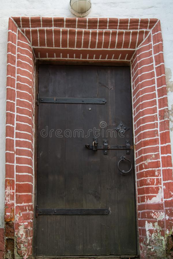 View of the old wooden door, forged metal hinges, locks, beautiful decorative finish outside with brick. Architecture, elements royalty free stock image