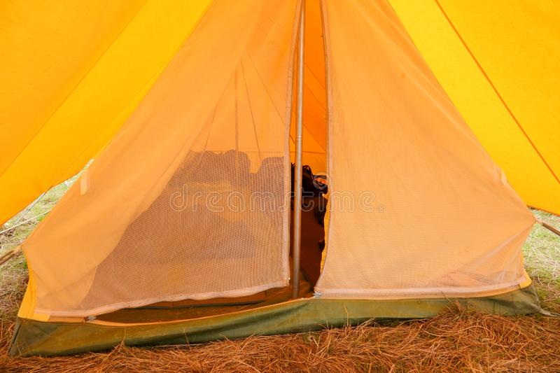 View in old yellow canvas camping tent with iron pegs. Old yellow canvas camping tent, vintage, grass, holiday, nature, outdoors, rural, shelter, travel stock photo