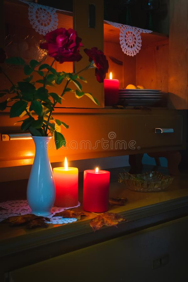 Old yellow painted cupboard with candles, a vase with red roses, autumn leaves and crocheted doilies. View of an old yellow painted wooden vintage cupboard with stock photography