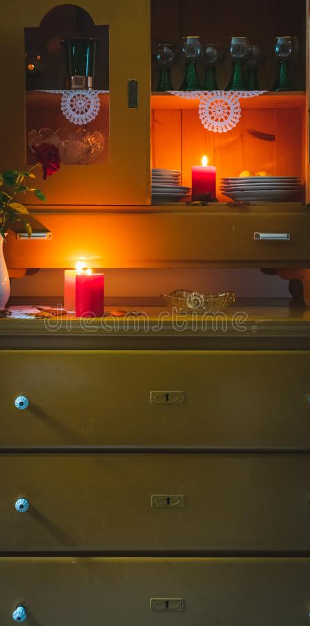 Old yellow painted cupboard with candles, a vase with red roses, autumn leaves and crocheted doilies. View of an old yellow painted wooden vintage cupboard with royalty free stock photography