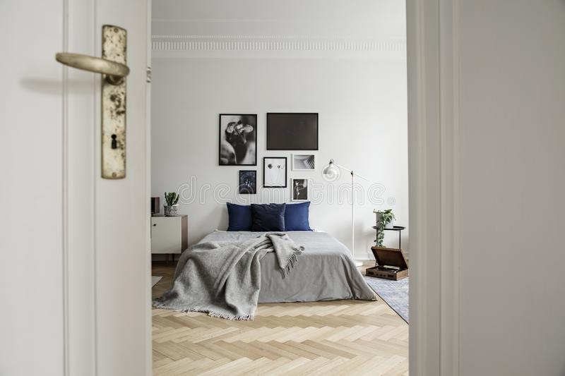 Spacious and natural bedroom interior with hardwood floor, art gallery and minimalist decor royalty free stock photo