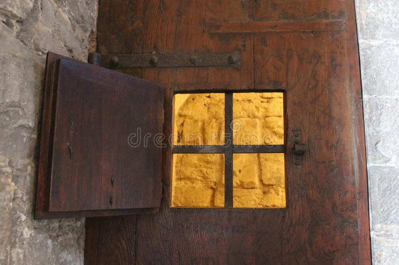 An open window with iron grid of an ancient door of a prison or a dungeon. stock photo