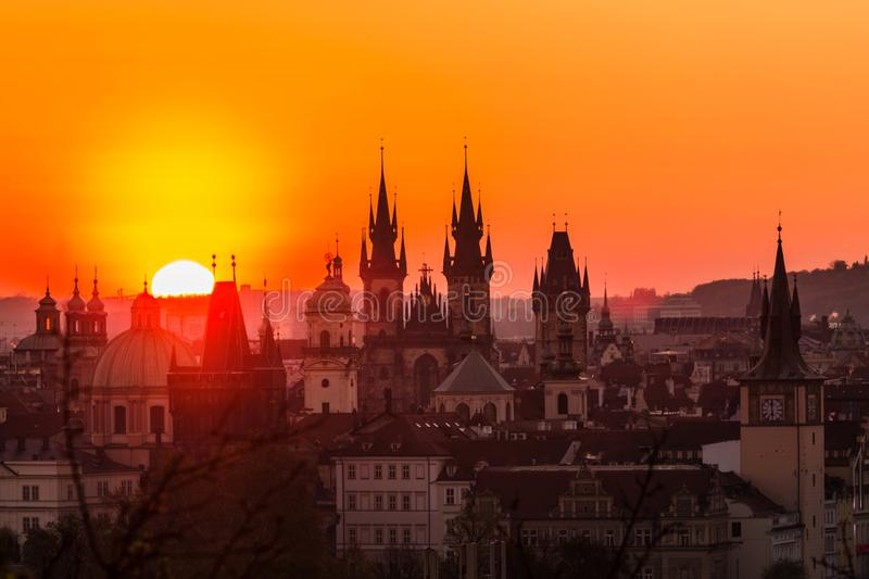 View of orange and pink sky during morning sunrise. In Prague, capital of the Czech Republic, sun shining behind black horizon with towers and spires, urban royalty free stock image