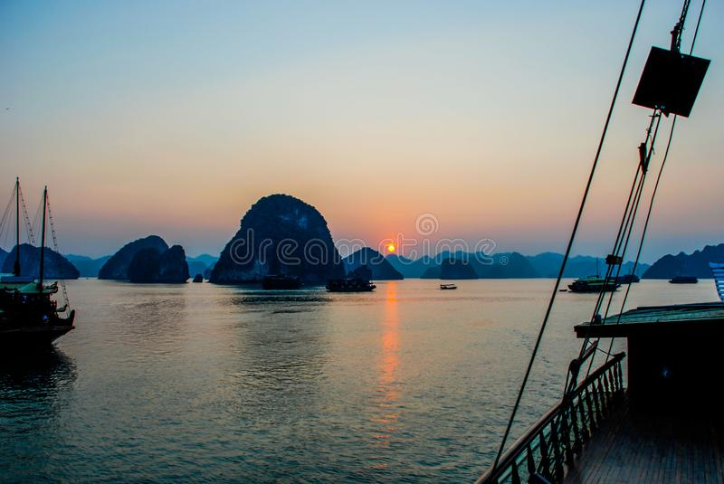 View of the orange setting sun on Ha Long Bay from the deck of a traditional boat. Blue and orange sunset on Ha Long Bay with silhouettes of traditional boats royalty free stock photo