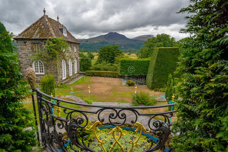 View on the orangerie and the surrounding landscape from the garden of Plas Brondanw, North Wales. View on the surrounding landscape and hills and the orangerie stock image