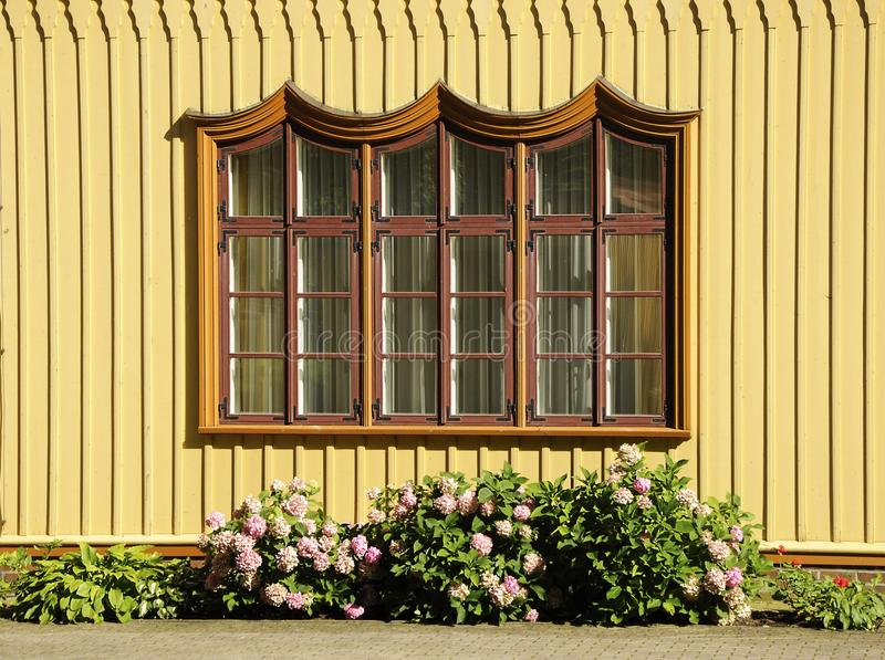Ornamented rustic window. A view of the ornamented window of a wooden rustic cottage in Lithuania royalty free stock image