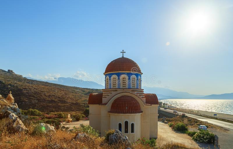 View of orthodox greek church at mediterranean coast. Orange foof, white building and blue sea waves. Crete island. Greece. Summer vacation stock photography