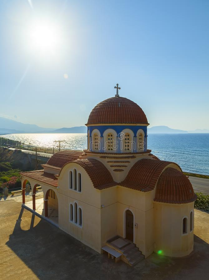 View of orthodox greek church at mediterranean coast. Orange foof, white building and blue sea waves. Crete island. View of orthodox greek church at royalty free stock photography