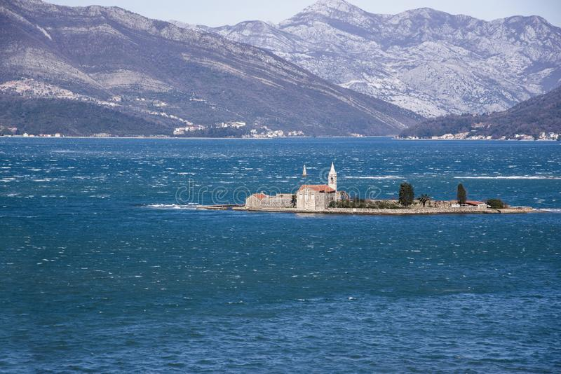 View of Otok Island Gospa od Milo Bay of Tivat, Montenegro, on a windy winter day. 2019-02-23 11:49. View of Otok Island Gospa od Milo with monastery of Order of royalty free stock images