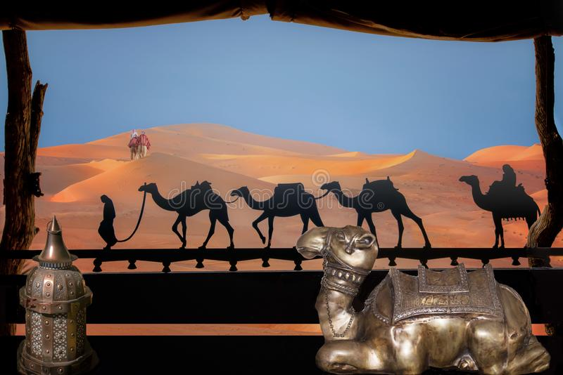 View out of luxury tent to dunes with arabian camels in Abu Dhabi. Tent decorated with lantern, laying camel, caravan silhouette. View out of window to orange stock photography