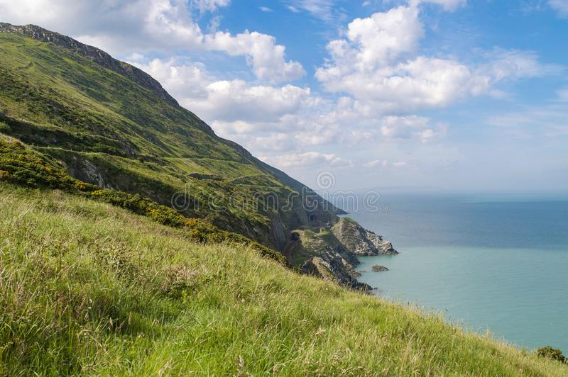 View over cliffs of Co. Wicklow Ireland of the Irish Sea and rail tunnel cut into the side of the mountain stock image