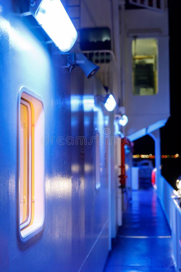 View from the outside on the ferry, porthole and blue illumination at night.  stock photo