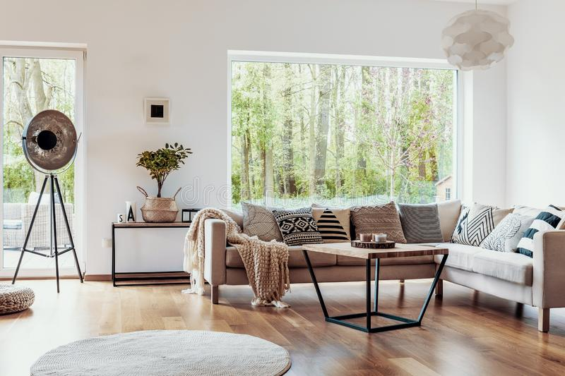 View outside to the green woods through large glass windows in a natural living room interior with beige sofa and dark hardwood fl stock photos