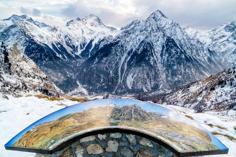 View from outskirts of Les deux Alpes village on mountain range and valley below with map on stone table. French alps, Auvergne Rhone region, France stock photography