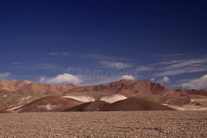 View over barren plain on brown hills contrasting with deep blue sky - Salar Salt flat near San Pedro de Atacama - Chile. View over barren plain on brown hills stock images