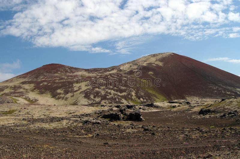 View over barren wide plain on red and green bare hills contrasting with blue sky and cumulus clouds - Iceland stock images