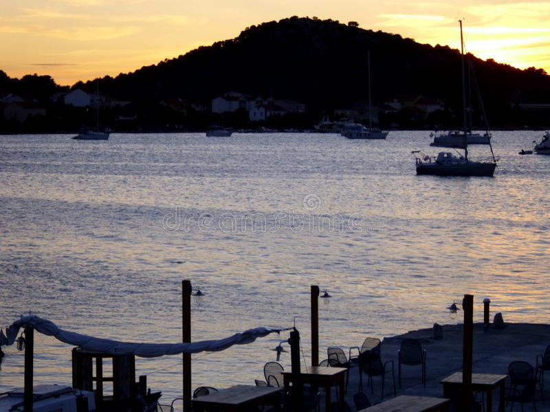 View over a bay, in the foreground the terrace of a restaurant, boats anchoring in the water. In the dark background a hill, taken in the last sunlight royalty free stock photo