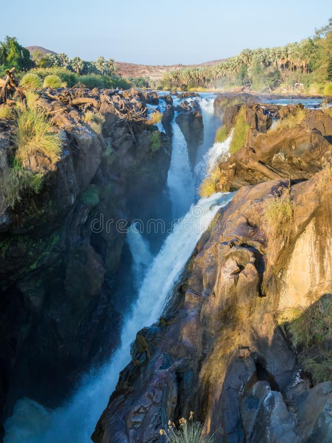 View over beautiful scenic Epupa Falls on Kunene River between Angola and Namibia in evening light, Southern Africa.  stock photo