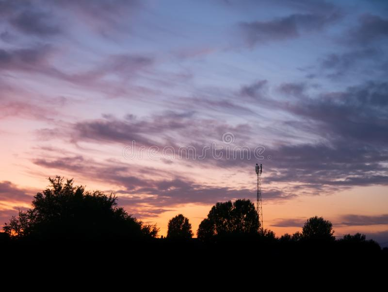 View over a beautiful sunset behind a radio antenna tower stock image