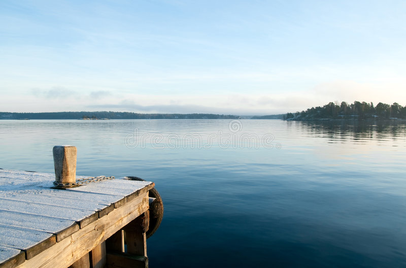 View over a calm lake. View from the jetty over a calm lake in the evening stock image
