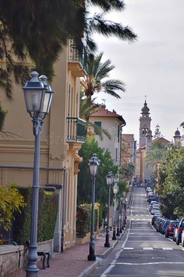 View on a city street in Bordighera. View over a city road in Bordighera, Italy. In the background the church bell tower royalty free stock photos