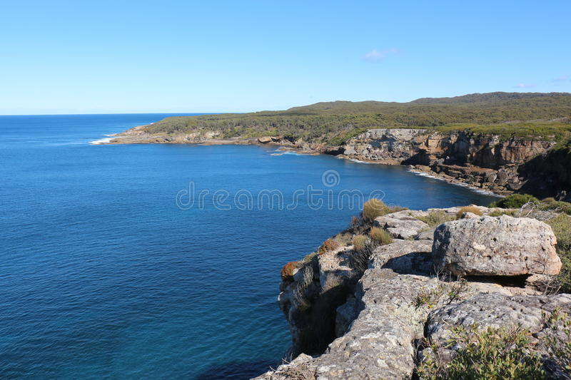 View over cliff face in Jervis Bay National Park, Australia. Stunning view over the cliffs that jut over the Pacific Ocean in Jervis Bay National Park, Australia stock images