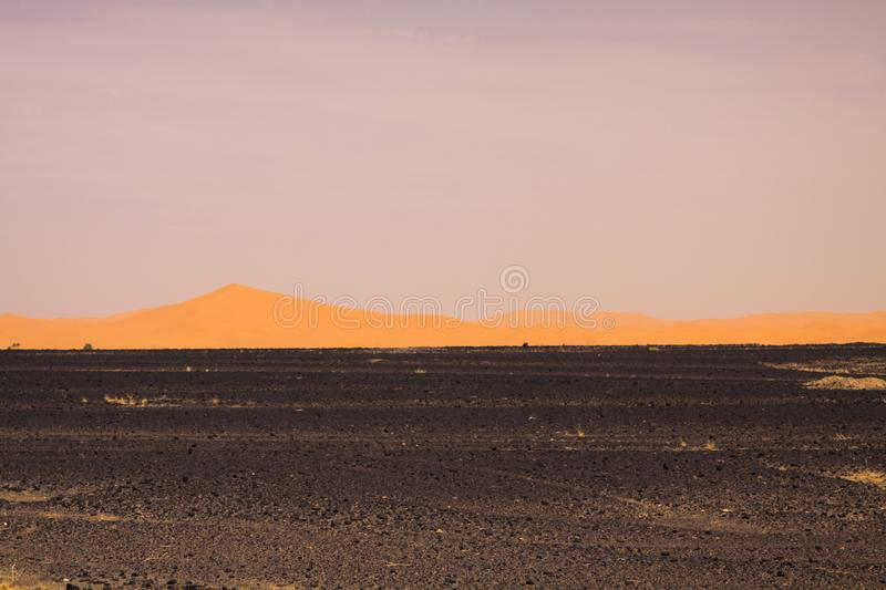 View over endless burned black flat waste stony land on golden sand dunes and blurred gloomy sky, Erg Chebbi, Morocco stock photo
