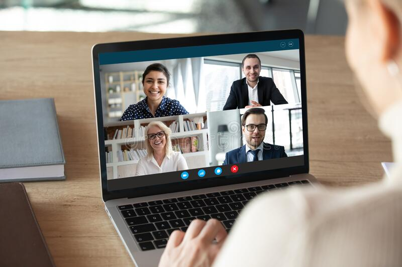 Computer screen view diverse businesspeople negotiating distantly using videocall. View over female shoulder at computer webcam screen view of four different age stock photography
