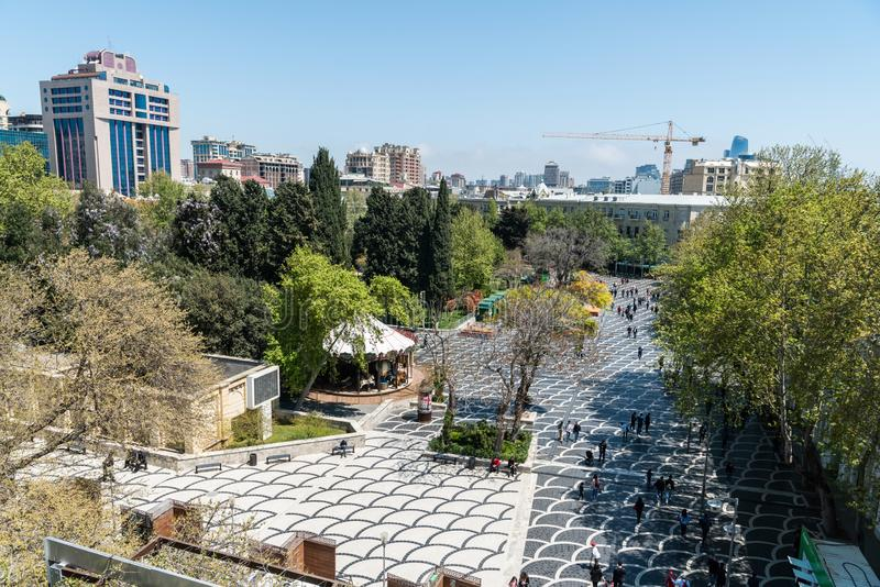 View over the Fountains Square in Baku, Azerbaijan. Baku, Azerbaijan - April 27, 2019. Fountains Square in Baku, with buildings, vegetation and people royalty free stock photo